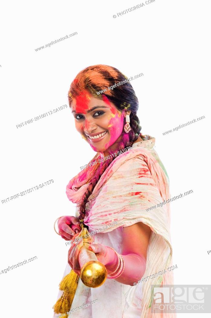 Stock Photo: Woman playing Holi with a pichkari.