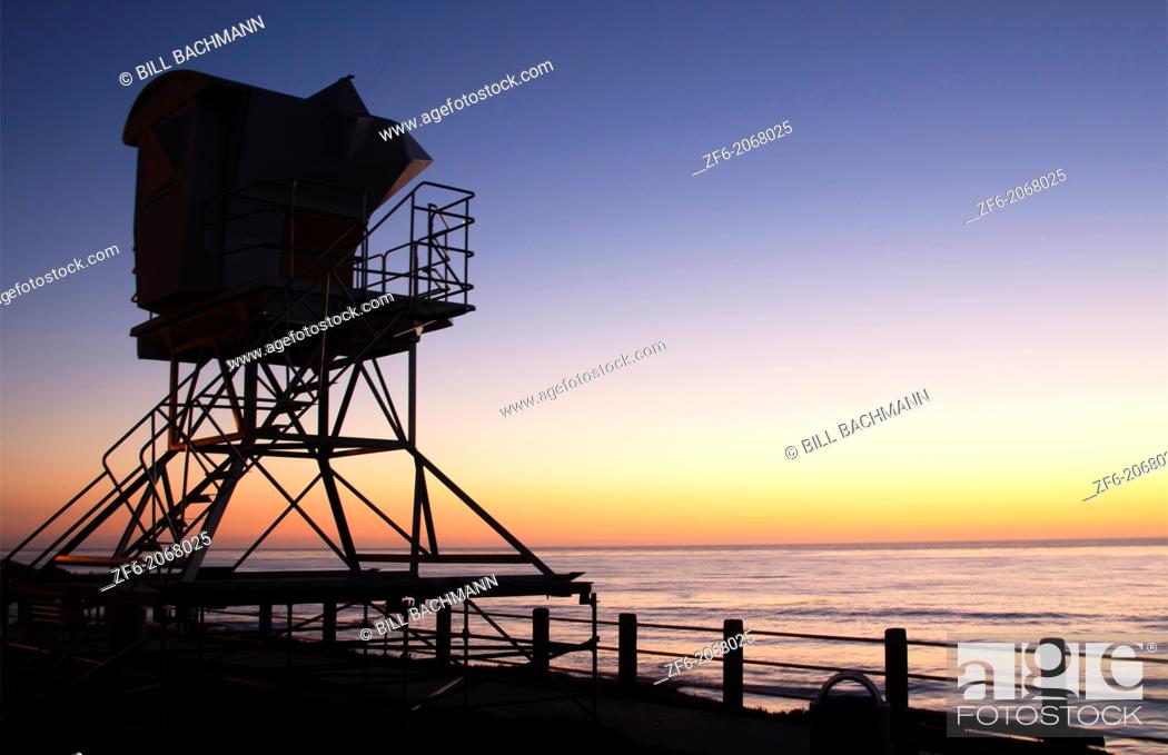 Stock Photo: San Diego California CA La Jolla sunset at The Cove with beach and lifeguard stand with beach at twilight.