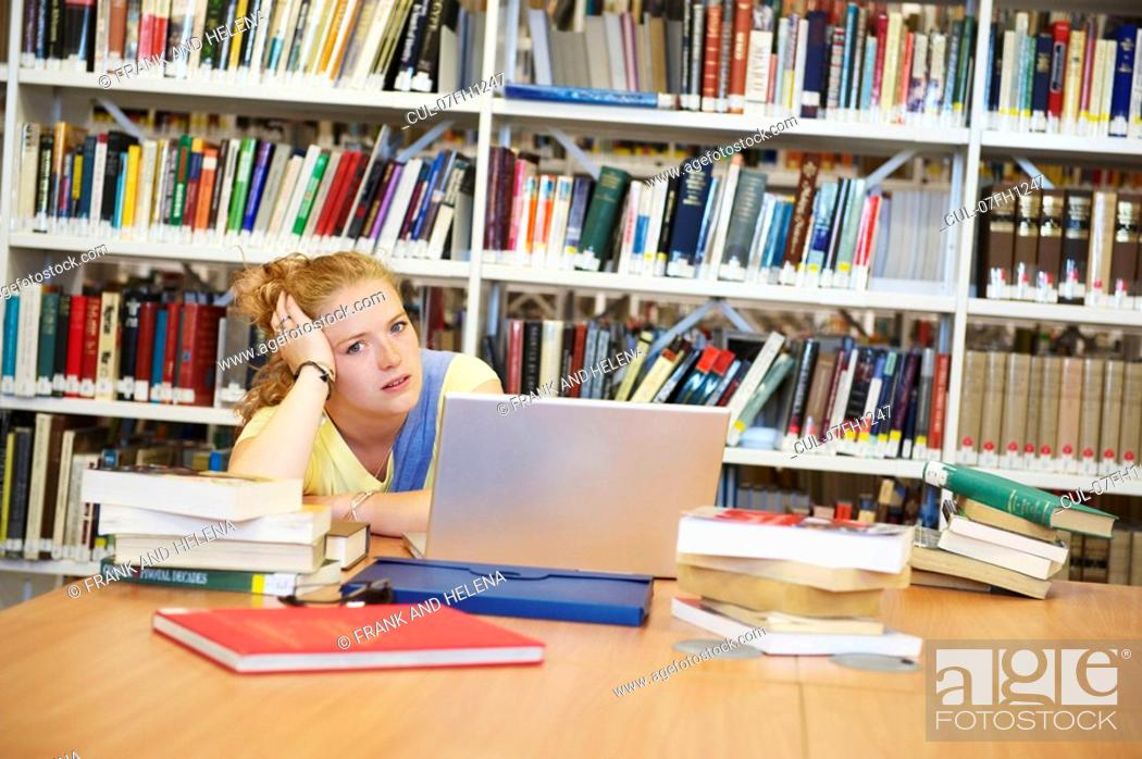 Stock Photo: Bored young woman in library.