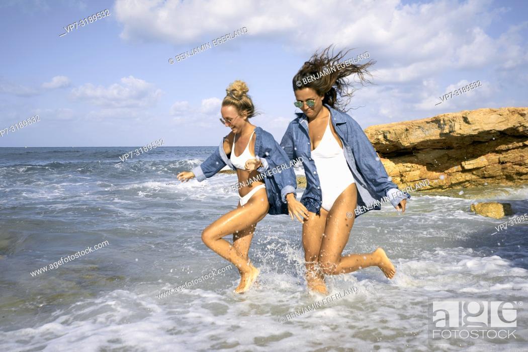 Stock Photo: Two women running in sea water at beach, Chersonissos, Crete, Greece.