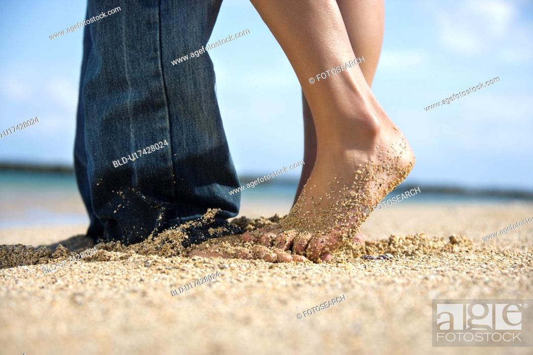 Stock Photo: Feet and legs of mid-adult Caucasian couple standing together on beach.