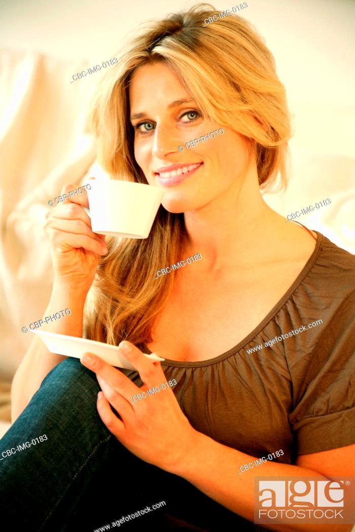 Imagen: Portrait of Young Woman Having a Cup of Coffee, Sitting on Sofa.