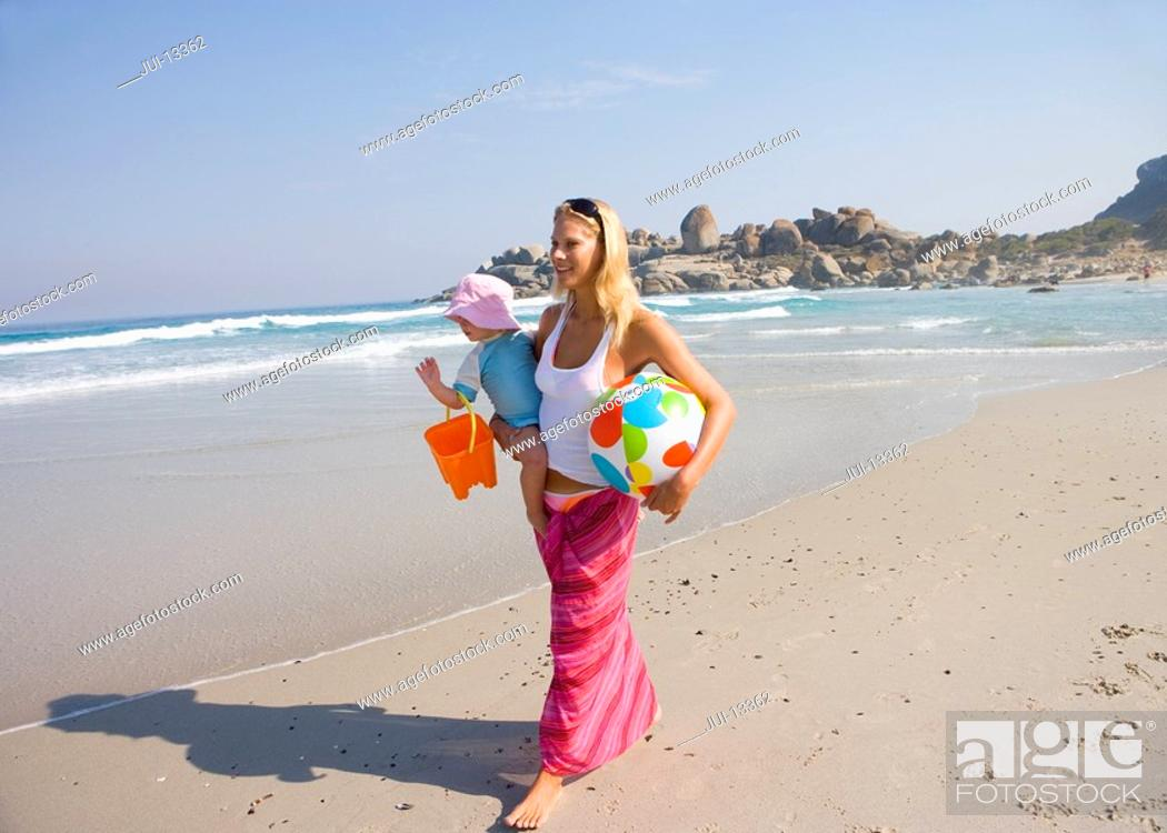 Stock Photo: Mother walking on beach with daughter 12-15 months, smiling.