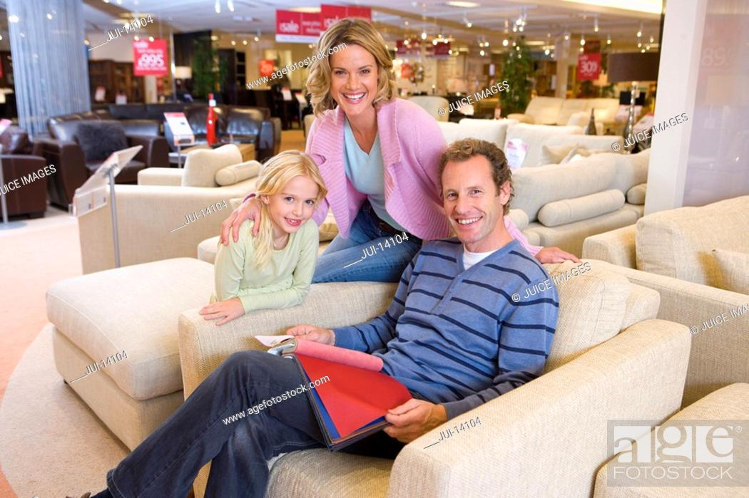 Stock Photo: Family of three in furniture shop, man in armchair, smiling, portrait.