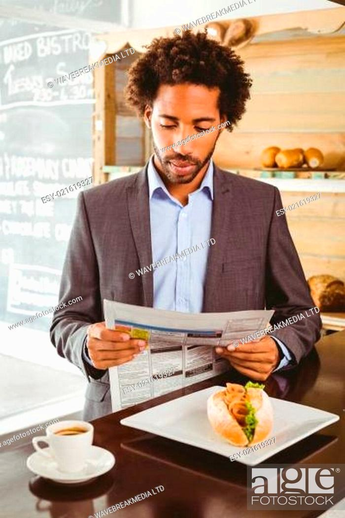 Stock Photo: Businessman reading newspaper while having lunch.