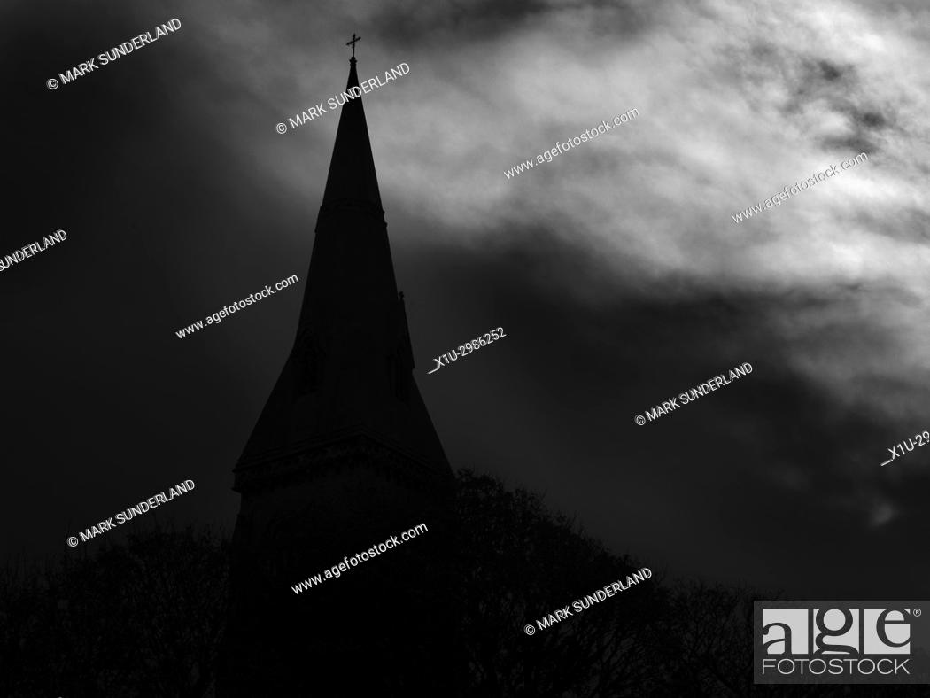Imagen: Silhouette of a Church Spire against a Dark Cloudy Sky. North Yorkshire, England.