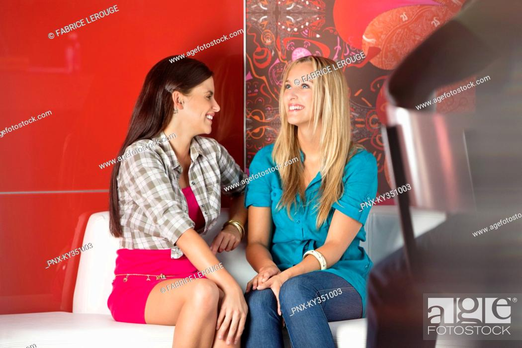 Stock Photo: Female friends sitting on a sofa in a cafe.