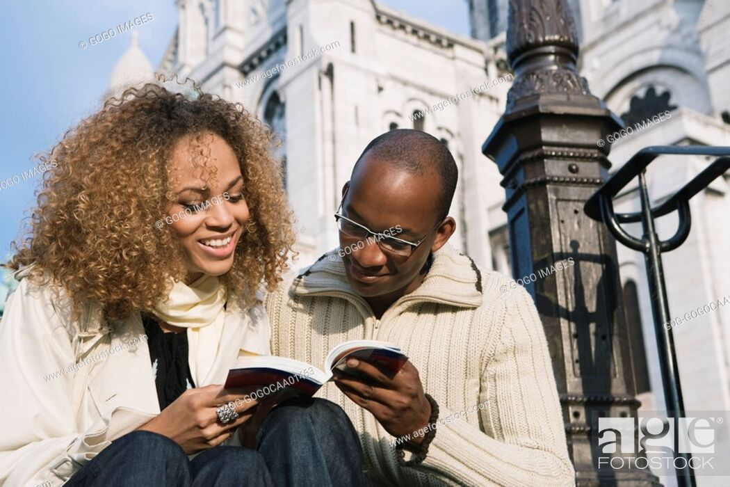 Stock Photo: African couple looking at guidebook.