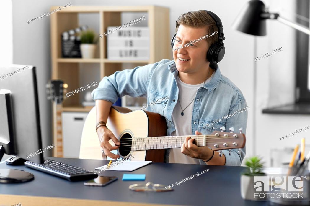 Imagen: man in headphones playing guitar at home.