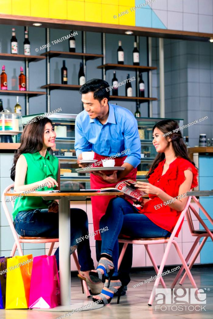 Stock Photo: Side view of a handsome and polite waiter smiling while serving coffee at the table of two beautiful young women in a trendy coffee shop.