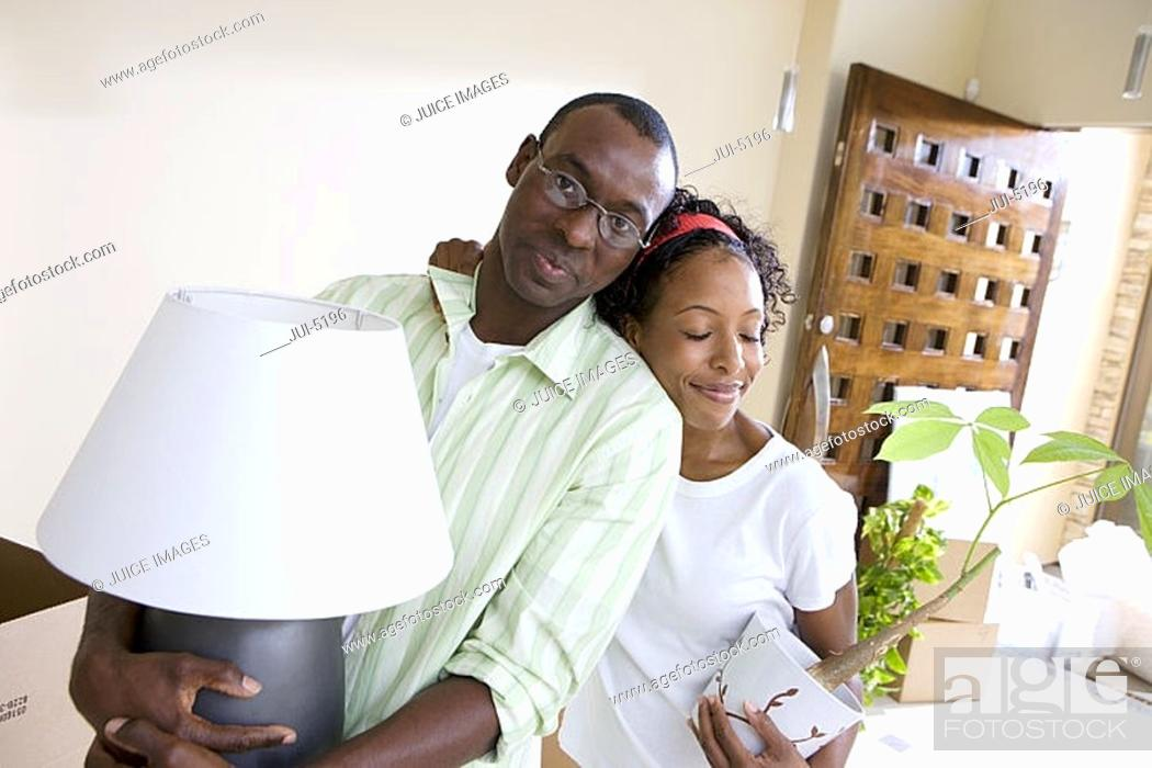 Stock Photo: Couple moving house, woman with pot plant embracing husband, man carrying lamp, portrait tilt.