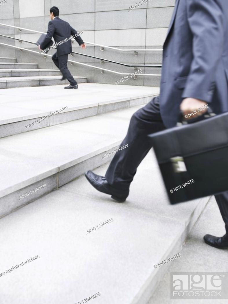 Stock Photo: Business men hurrying up steps outdoors side view.