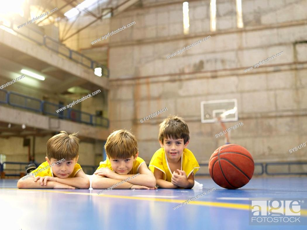 Photo de stock: Boys lying on floor near basketball portrait.