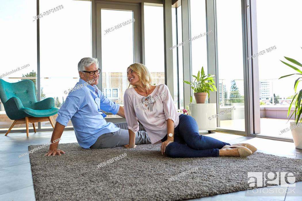 Stock Photo: Smiling mature couple relaxing at home sitting on carpet.