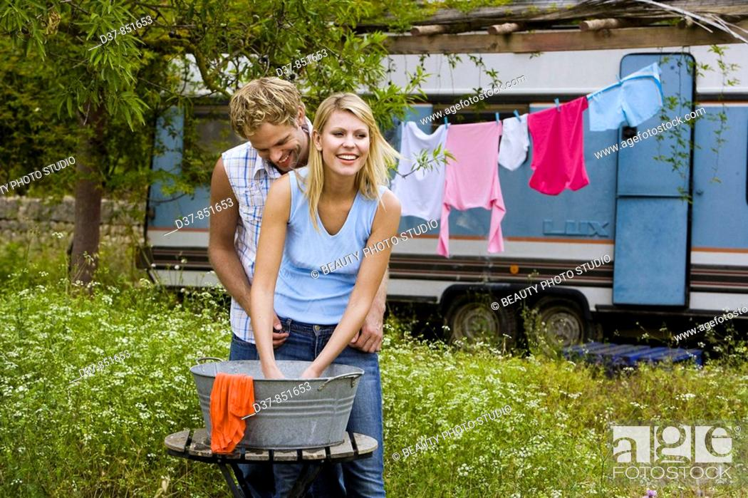 Stock Photo: Couple doing the washing with affection outdoors.