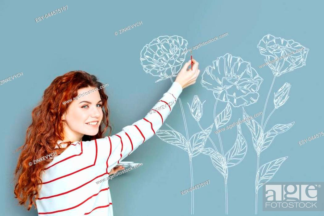 Stock Photo: Creative person. Talented young painter holding a brush and painting a beautiful flower on the wall.