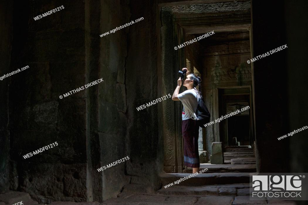 Stock Photo: Cambodia, Siem Reap, Angkor Thom, tourist taking pictures of Bayon temple with camera.