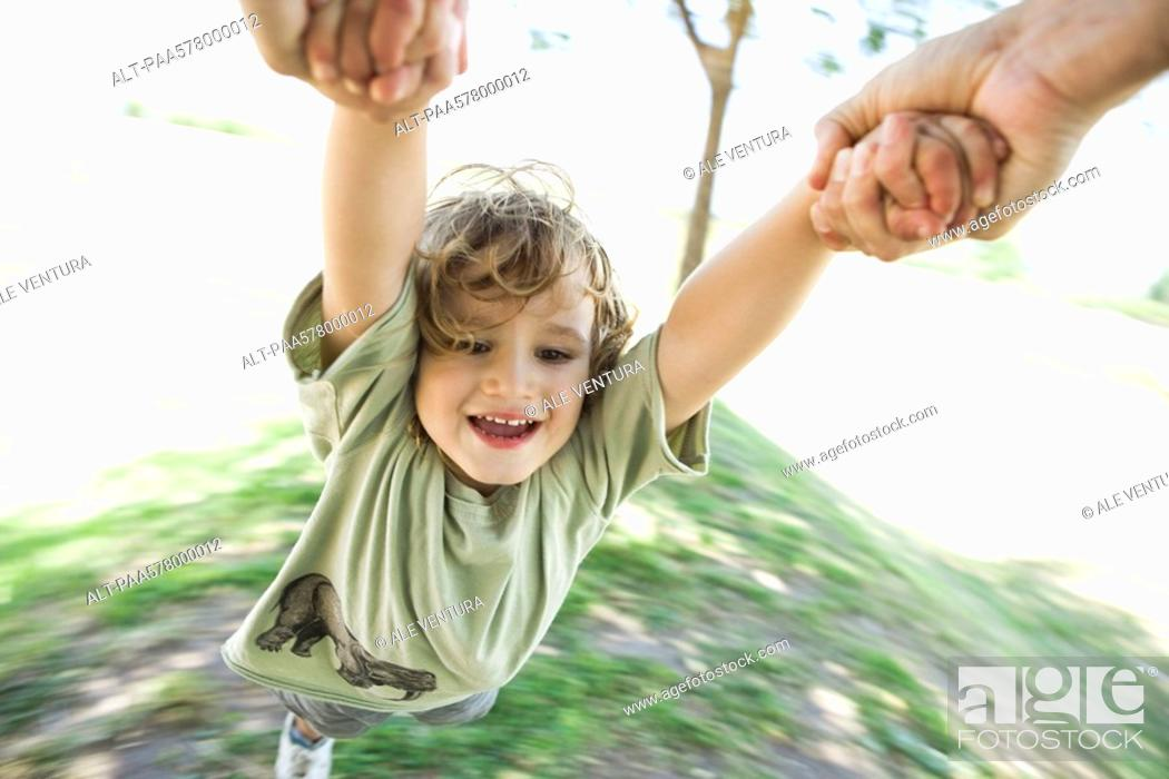 Stock Photo: Boy being swung through air by his arms.