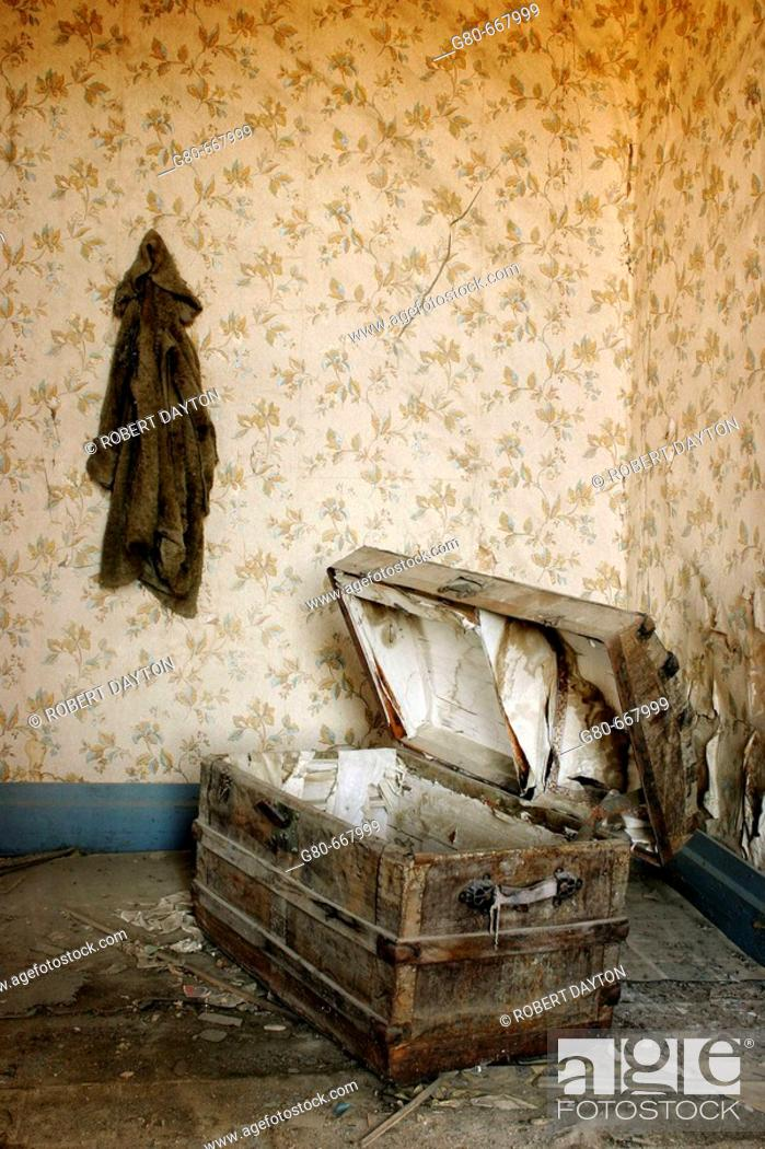 Stock Photo: A coat hangs on the wall above an open trunk in a Bodie residence, CA, USA.