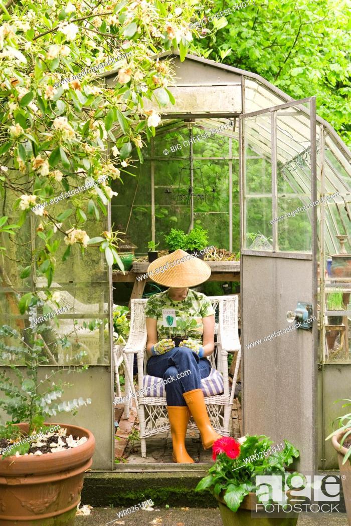 Stock Photo: Woman sitting in backyard greenhouse.