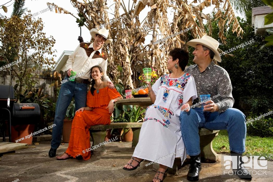 Imagen: Portrait of a cheerful Tex-Mex family sitting together in the backyard of house.