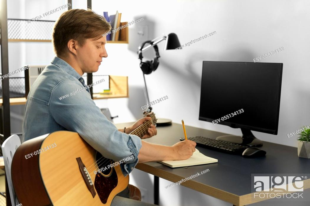Imagen: man with guitar writing to music book at home.