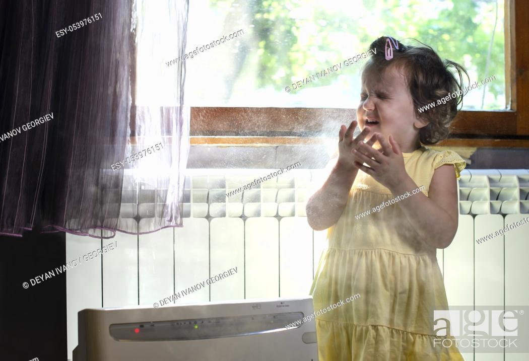 Stock Photo: Little girl in a dusty room. Air purifier and coughing kid. Dust in the air. Allergy concept.