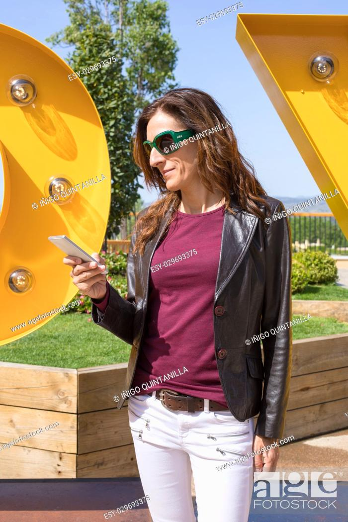 Stock Photo: brown hair woman with white jeans, red shirt, leather blazer jacket and sunglasses, standing in urban park, looking and typing on mobile smart phone.
