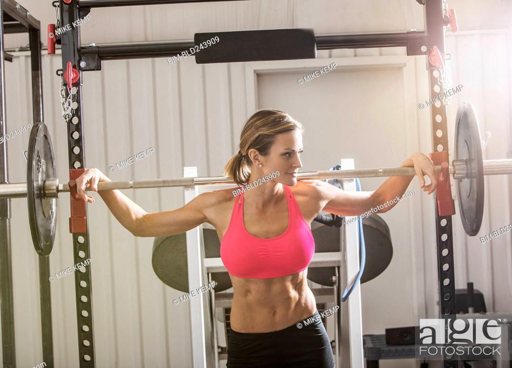Stock Photo: Woman lifting barbell in gymnasium.
