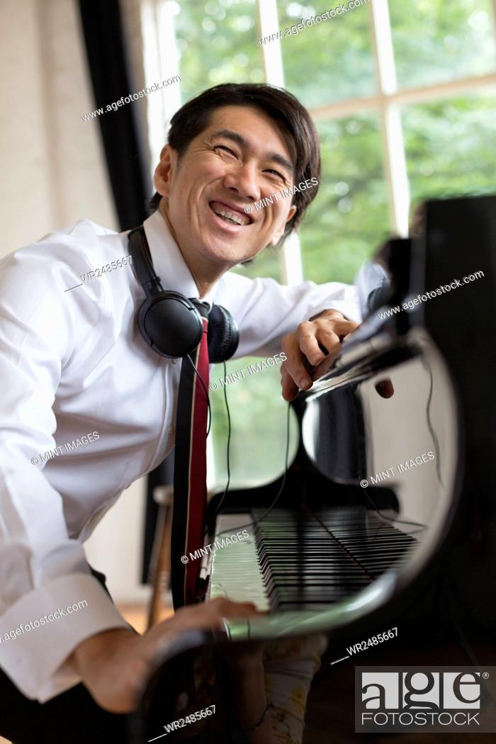 Imagen: Young smiling man sitting at a grand piano in a rehearsal studio, wearing headphones round his neck.