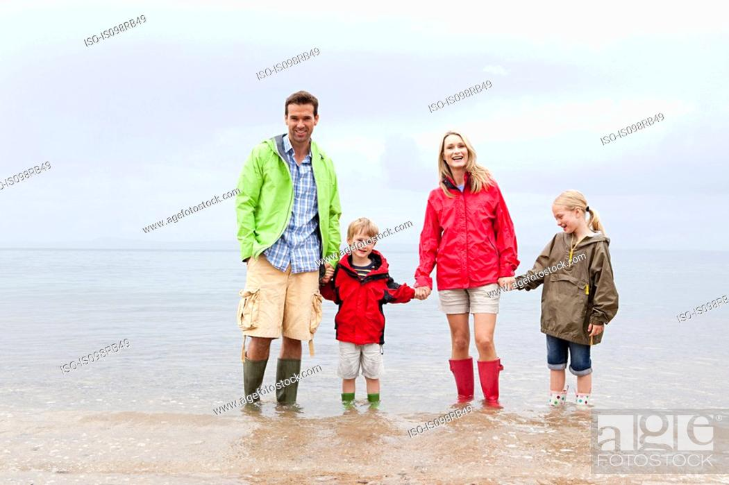 Stock Photo: Family holding hands in the sea.