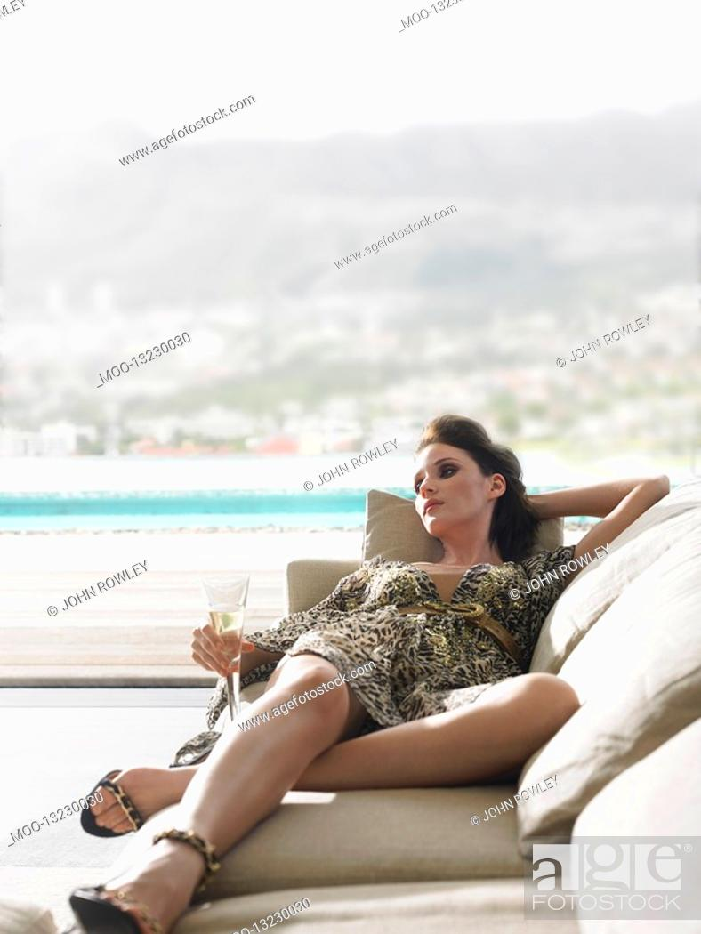 Stock Photo: Woman reclining on sofa with champagne on balcony.