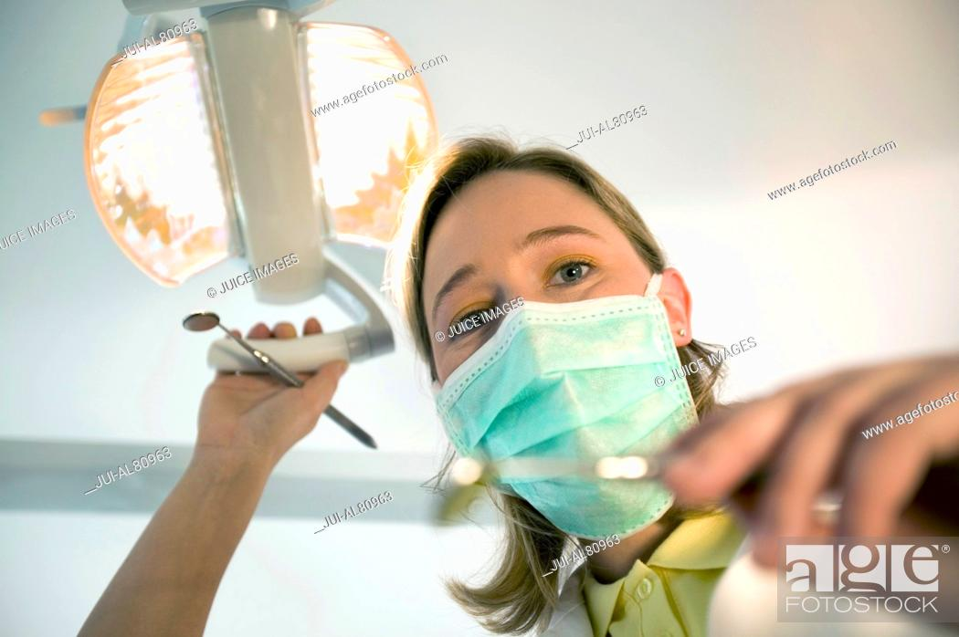 Stock Photo: Female dentist wearing surgical mask and holding dental tools.