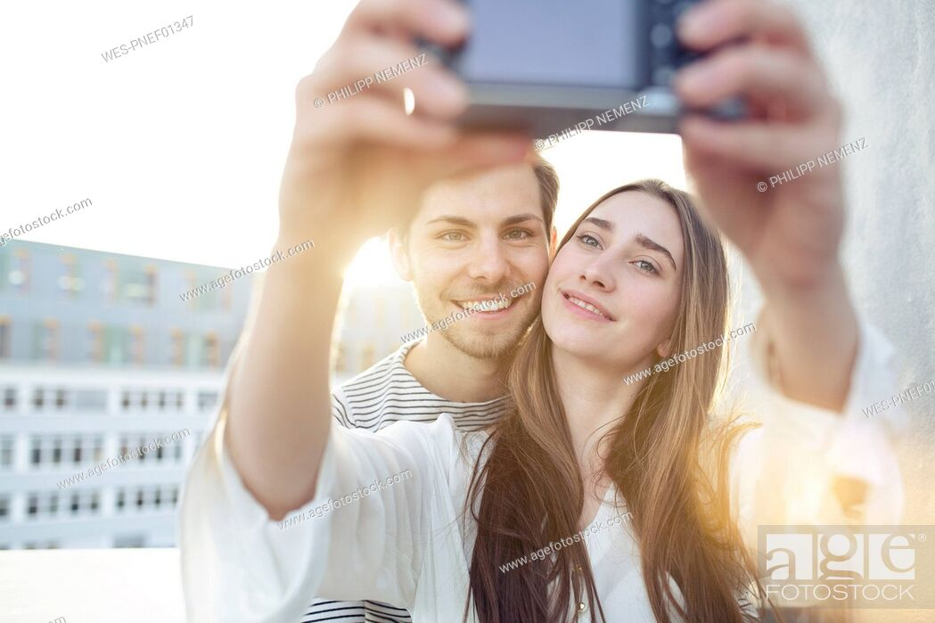 Stock Photo: Smiling young couple taking a selfie outdoors.