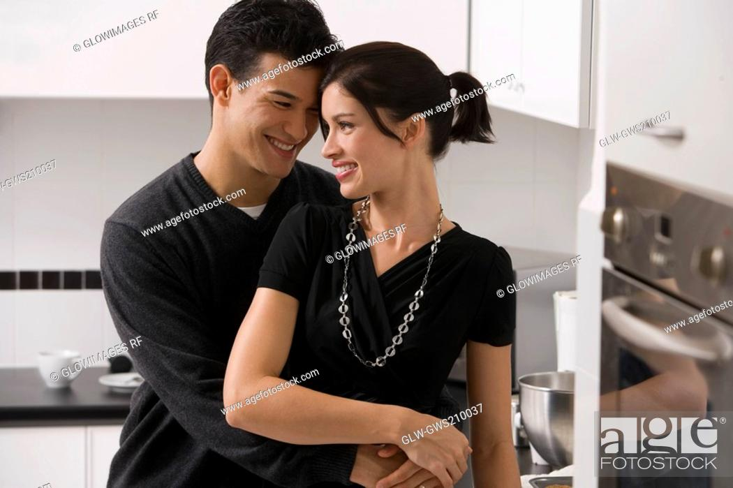 Stock Photo: Young couple romancing in the kitchen.