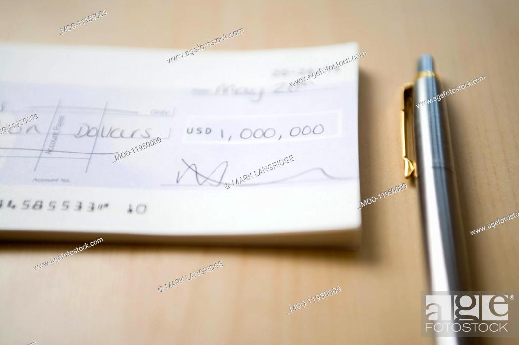 Stock Photo: Cheque for one million dollars lying next to pen on table close-up.