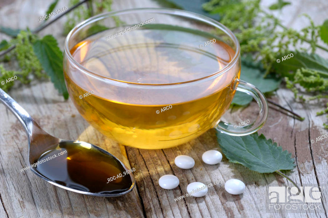 Stock Photo: Cup of tea Nettle juice and Nettle pills Urtica dioica.