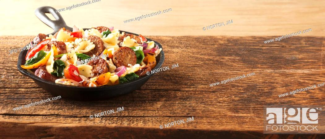 Stock Photo: Farfalle pasta with sausage and peppers.