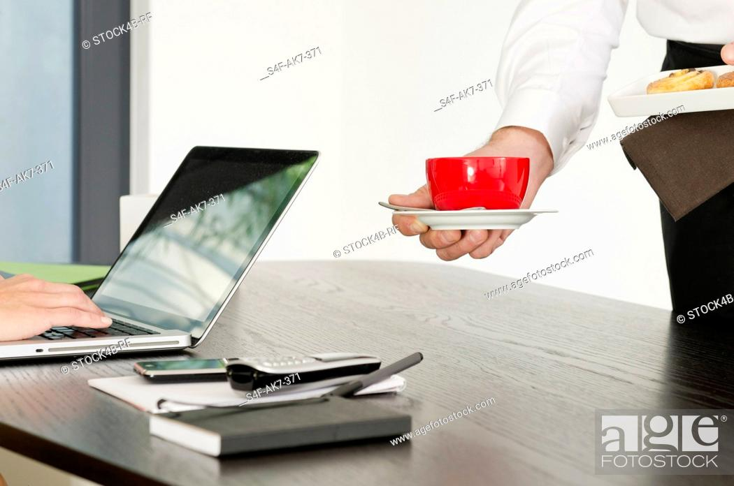 Stock Photo: Coffee and pastry is being served for woman at desk.
