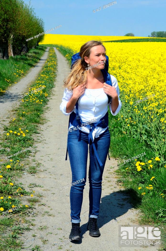 Stock Photo: Young woman with backpack walking on a countryroad with willow trees and field of rape in Skivarp, Scania, South Sweden.