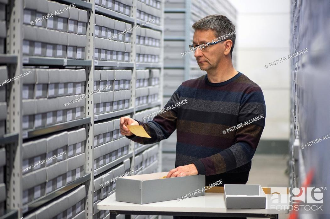 Stock Photo: 11 December 2018, Hessen, Bad Arolsen: Christian Groh, Head of the Archive Department, browses between file cabinets in the provisional archive of the.