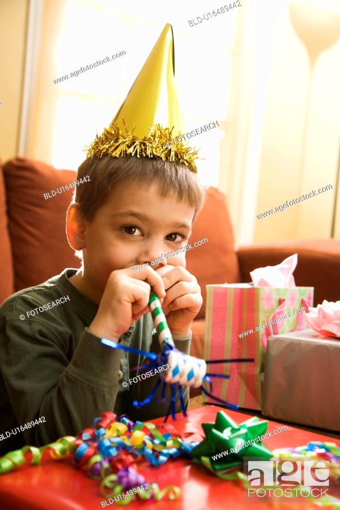 Stock Photo: Boy at birthday party looking at viewer blowing noisemaker.