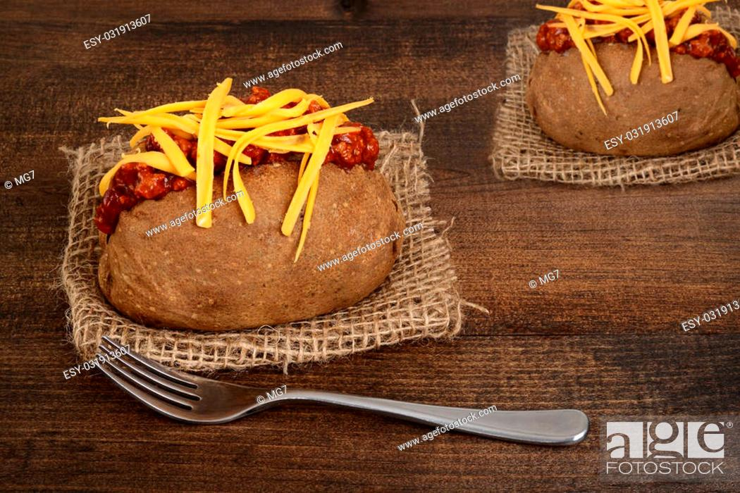 Stock Photo: chili and cheese baked potato with fork on wood.