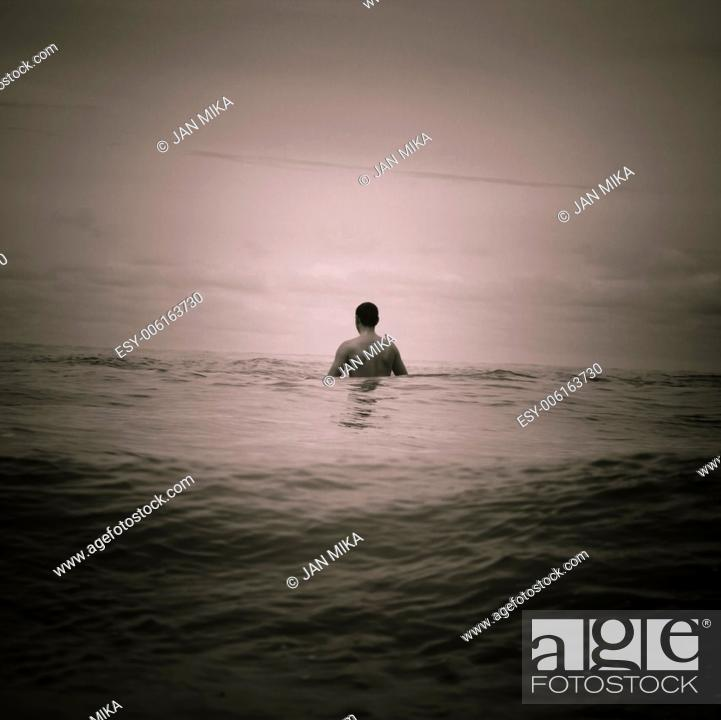 Stock Photo: Abstract toned photo of man in the sea.