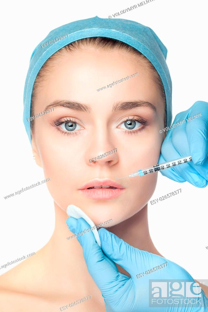 Stock Photo: Attractive woman at plastic surgery with syringe in her face on white background.