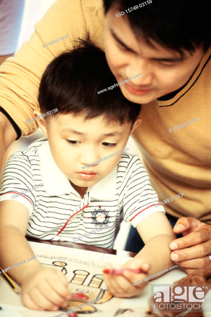 Stock Photo: Father helping his son draw with crayons.