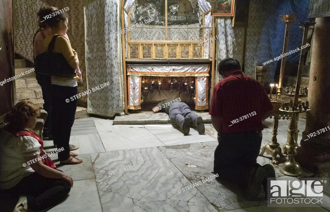 Stock Photo: Worshipers at the site where Jesus Christ was born, church of the nativity, Bethlehem, Palestine.