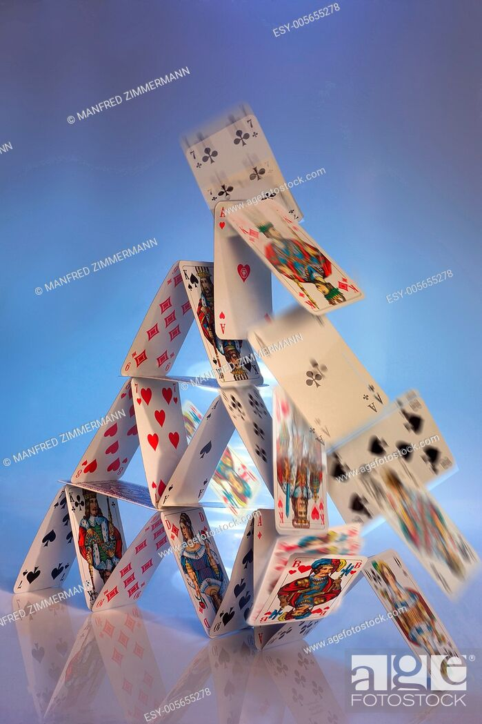 Stock Photo: Falling house of cards together as a symbol of collapse.