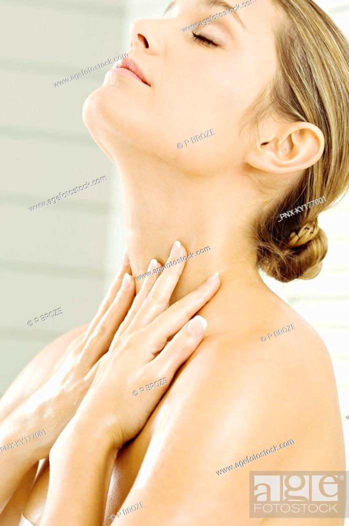 Stock Photo: Close-up of a young woman applying moisturizer on her neck.