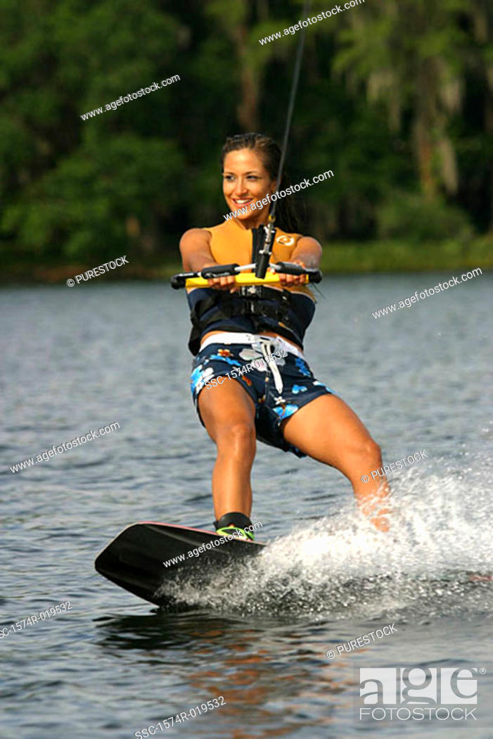 Stock Photo: Young adult woman wakeboarding, Florida, USA.